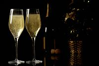 Two champagne glasses, champagne bottle and Christmas tree on black background.