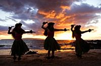 Three hula dancers at sunset at Palauea Beach, Maui, Hawaii.