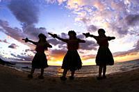 Three hula dancers at sunset, Maui, Hawaii.