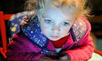 3-year-old girl : eyes too close to a tablet of computer.