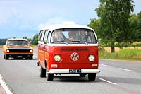 Classic Volkswagen red and white Type 2 camper van moves along highway on Maisemaruise 2017 car cruise summer event in Tawastia Proper, Finland. Publi...