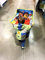 A small boy pushes a folding chair down an isle in a large, modern store, Halifax, Canada.