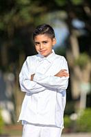 Elegant young man in white clothes posing for the camera in a photo shoot.