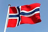 Norway's Flag on flagpole against blue sky.