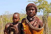 Woman from Hamar tribe with her baby boy standing at road side, Ethiopia, East Africa.