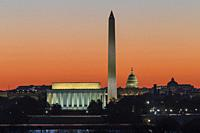 The Lincoln Memorial, Washington Monument, and US Capitol building set against an orange sky during morning twilight in Washington, DC.