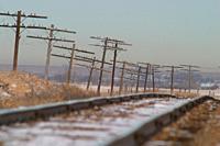 Wobbly improvised looking powerlines and rail tracks. Alberta praerie, west of Dinosaur Provincial Park along Hwy 1. Alberta, Canada.
