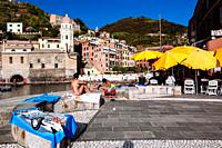 Tourists on the beach and having sunbaths, Vernazza, Italian Riviera, Liguria, Italy.