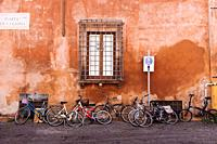 Bicycles parked against a colourful wall in Trastevere neighbourhood, Rome, Lazio region, Italy.