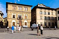 Tourists walking by classic buildings in Piazza Santa Croce, Florence, Tuscany, Italy.