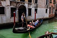 Gondola full of tourists on a canal, Venice, Veneto, Italy.