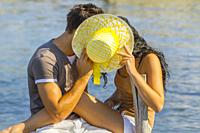 Young couple Summer vacation hiding behind Yellow hat.