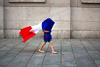 A child playing with the flag of France, celebrating the victory of the national team in the World Cup 2018. Latin Quarter, Paris, France.