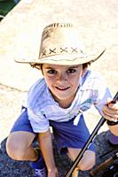 portrait of a 10 year old boy with a cowboy hat.