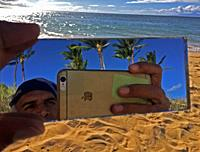 A man combines the sea, the sand, and the trees in a selfie on the beach, Maui, Hawaii, USA.