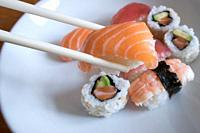 Fresh salmon nigiri sushi between chopsticks with uramaki, prawn nigiri and tuna nigiri in the background.
