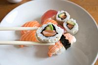 Fresh salmon and avocado uramaki sushi between chopsticks with salmon nigiri, prawn nigiri and tuna nigiri in the background.