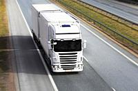 White refrigerated trailer truck transports perishables goods on motorway, motion blur, above view.