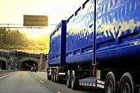 Blue heavy transport truck drives on motorway among traffic towards a road tunnel and evening sunset.