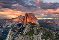 Vivid summer storm clouds at sunset above Half Dome and Glacier Point in Yosemite National Park, USA.