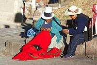 Indigenous women in traditional clothing sewing at the side of the street in the historic center, Cusco, Peru, South America