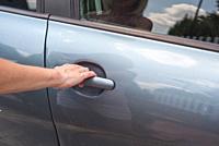 Woman hand opening car door close up.