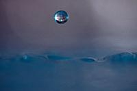 A drop of blue water suspended above the surface of the water