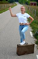 Hitch-hiking young woman, 25 years old, on a countryroad in Scania, Sweden; Europe, standing with one foot on an old suitcase.
