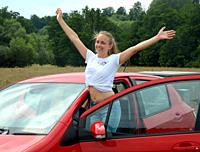 Young woman, 25 years old, stand smiling at a car and rising her arms on a country road in Scania, Sweden, Europe.