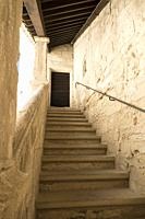 Stone steps ascending, with wooden roof beams appearing to descend in a repeating geometric pattern to meet an old wooden door set in the sunlit chalk...