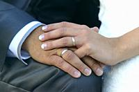 Close-up of wedding rings and hands of the bride and groom