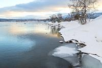 Winter landscape in Tjåmotis with mountains in background, sun shining over the mountains, creek with open water, sky with nice colors reflecting in t...