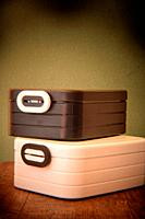 Two lunch boxes sitting on wooden table. Shot with Holga lens for selective focus.