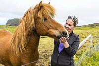 A local guide with an Icelandic horse, Heimaey Island, in the Westman Island Group, Iceland.