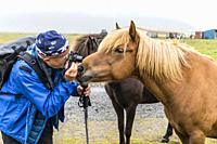 Photographer with Icelandic horses on a farm on the southeast coast of Iceland.