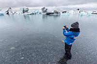 Girl photographing calved ice from the Breidamerkurjokull glacier in Jökulsárlón glacial lagoon, Iceland.