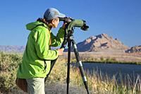 Birder with spotting scope, City of Henderson Bird Viewing Preserve, Nevada.