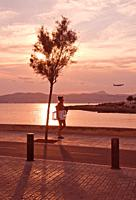 MALLORCA, SPAIN - JULY 21, 2012: Woman walks home from the beach in beautiful landscape at sunset on a sunny summer evening on on July 21, 2012 in Mal...