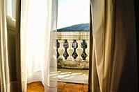 Behind net curtain drapes leads to the balcony at the Hotel Imperial in Opatija, Croatia.
