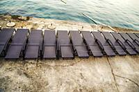 Empty beach chairs lined up like black paino keys on the waterfront at sundown in Opatija on the Adriatic sea in Croatia.