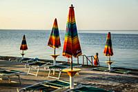 Empty beach chairs with large folded down umbrellas line the waterfront at sundown in Opatija on the Adriatic sea in Croatia.
