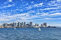 Sailboats gliding by Harbor Bay in San Diego, California.