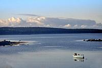 A boat moored in a calm sea in a cove of the Atlantic Ocean, Nova Scotia, Canada.