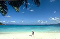 A mature woman walks toward the water on a white-sand beach of the Indian Ocean, Mahe, the Seychelles.