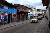 Bogotá, Colombia - May 28, 2017: Traffic drives past some Street Art and Graffiti in the historic La Candelaria district in the capital city of Bogota...