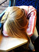 Someone has had a rough week. Woman on train from Heerlen to Maastricht. Sitting with head resting on table.