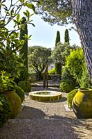 small garden in the Provence with fountain and amphores, old village Ménerbes, situated on a hill, department Vaucluse, Luberon mountains.
