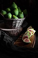 Still life with figs inside a basket on an old wooden table.