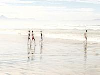 Four young boys having fun during at day at the seaside.