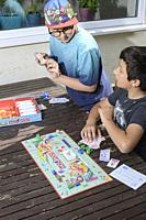 Young boys,10-11 years old play monopoly board game,UK.